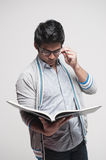 Asian Male Student reading a book. Attractive asian student holding glasses reading a book Stock Images