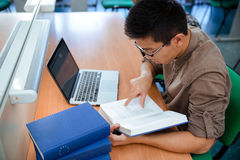 Asian male student reading book. Portrait of asian male student reading book in university Stock Image