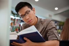 Asian male student reading book in university. Portrait of a handsome asian male student reading book in university Royalty Free Stock Photo