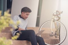 Asian male student sitting at the stairs and smiling as use lapt. Op computer with his bike background at campus,Students and education concept Royalty Free Stock Photography