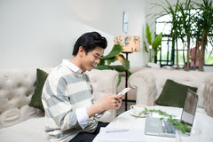 Asian male student texting by phone while sitting at the cafe sh. Op Royalty Free Stock Photo