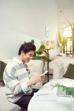 Asian male student texting by phone while sitting at the cafe sh. Op Stock Images