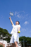 Asian Male Tennis Player. An Asian male tennis player is teeing off at the tennis court, wearing white tennis clothes Stock Photography