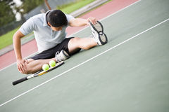Asian male tennis player. An asian male tennis player stretches before playing Stock Images