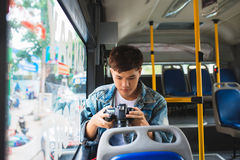 Asian male tourist photographing the city from the window of the. Bus Royalty Free Stock Image