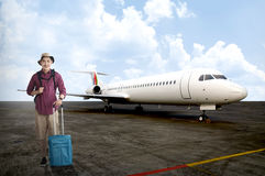 Asian Male Tourist. Posing in front of jet plane Stock Photo