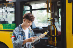 Asian male tourist reading a map at bus station. Asian male tourist reading a map at bus station Stock Photo