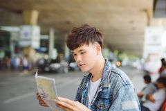 Asian male tourist reading map while waiting for taxi at the air Royalty Free Stock Images