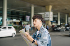 Asian male tourist reading map while waiting for taxi at the air.  Stock Images
