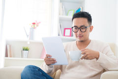 Asian male using computer tablet. Southeast Asian male drinking coffee / tea and using digital computer tablet at home Royalty Free Stock Photography