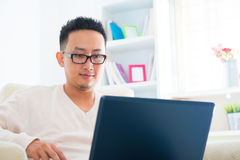 Asian male using notebook. Southeast Asian male using notebook sitting on sofa at home, living lifestyle Royalty Free Stock Photo