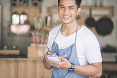 Asian male waiter in apron writing order. Happy asian male waiter in apron writing order and looking at camera Stock Image
