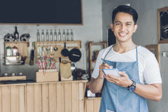 Asian male waiter in apron writing order. Happy asian male waiter in apron writing order and looking at camera Royalty Free Stock Image