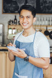 Asian male waiter in apron writing order. Happy asian male waiter in apron writing order and looking at camera Stock Photo