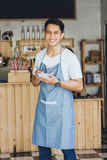 Asian male waiter in apron writing order. Happy asian male waiter in apron writing order and looking at camera Stock Photography