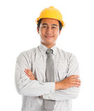 Asian male wearing yellow hardhat. Close-up of an Asian young man wearing a hardhat smiling and looking at camera, arms crossed standing isolated on white Royalty Free Stock Photos