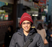 Asian male in winter chilling out in city. Asian male in winter hat in jacket stand around city with smile and relax expression Stock Image