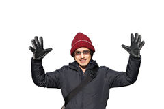 Asian male in winter hat in jacket raise hands isolated over whi. Asian male in red winter hat in jacket raise hands backpack traveler isolated on white Royalty Free Stock Photo