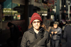 Asian male with winter jacket and hat stand  in city instagram t. Asian male in winter hat in jacket stand around city with smile and relax expression instagram Stock Photo
