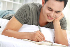 Asian male writing on notepad. While lying on the bed Royalty Free Stock Photos