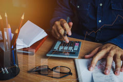 Asian man accountant or banker calculate finances / savings money or economy concept. Idea for save coin and accounting. Essential accessories on table office stock image