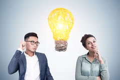 Asian man and African woman, light bulb Stock Images