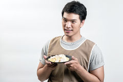 Asian man in apron with spaghetti carbonara Stock Images