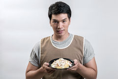 Asian man in apron with spaghetti carbonara Stock Photography