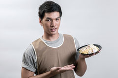 Asian man in apron with spaghetti carbonara Stock Photo