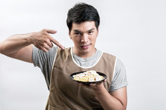 Asian man in apron with spaghetti carbonara Stock Image