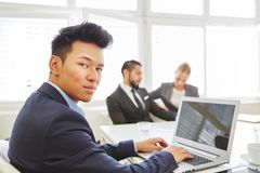 Asian man as competent programmer. Asian men as competent programmer using laptop computer in the office royalty free stock image