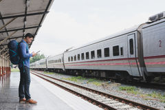 Asian man with backpack standing on platform at train station. b. Young asian man with backpack standing on platform at train station. backpacker or traveler Stock Photo