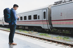 Asian man with backpack standing on platform at train station. b. Young asian man with backpack standing on platform at train station. backpacker or traveler Royalty Free Stock Photo