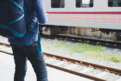 Asian man with backpack standing on platform at train station. b. Young asian man with backpack standing on platform at train station. backpacker or traveler Stock Images