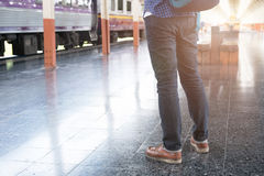 Asian man with backpack standing on platform at train station. b. Young asian man with backpack standing on platform at train station. backpacker or traveler Royalty Free Stock Photography