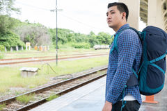 Asian man with backpack standing on platform at train station. b. Young asian man with backpack standing on platform at train station. backpacker or traveler Royalty Free Stock Photos