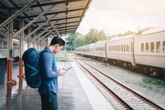 Asian man backpack for travel at train station and using tablet searching map location.  royalty free stock images