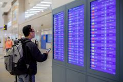 Asian man with backpack traveler using the smart mobile phone for check-in at the flight information screen in modern an airport stock photography