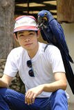 Asian man with beautiful Hyacinth macaw parrot Stock Images