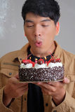 Asian man with birthday ice-cream cake on fire Stock Images