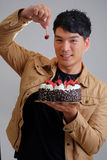 Asian man with birthday ice-cream cake on fire Royalty Free Stock Photo