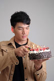 Asian man with birthday ice-cream cake on fire Stock Photography