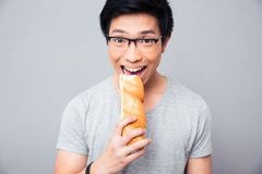 Asian man biting bread over gray background Stock Photo