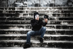 Asian man in the black hood and white mask with confused. Depression sitting on stairs and looking at black mask, in scary abandoned building, Human face Royalty Free Stock Photos