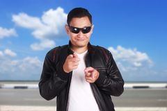 Asian Man in Black Leather Jacket Smiling and Pointing stock image