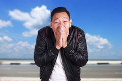 Asian Man in Black Leather Jacket Smiling Shy royalty free stock image
