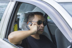 Asian man in black shirt in sunglass using smartphone Stock Photography