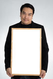 Asian man in black suit holds an empty white board Stock Images