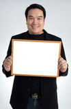 Asian man in black suit holds an empty white board Stock Photos