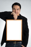 Asian man in black suit holds an empty white board Stock Photo